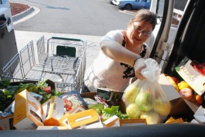 Campus Kitchen Coordinator Shelley Graves heaves bags of food into the Student Life van on a daily Fresh Market delivery.